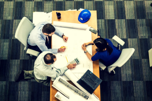 Aerial view of a group of three marketers working together at a desk.