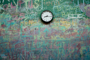 A clock mounted to a chalkboard is surrounded by muddled messaging and writing.